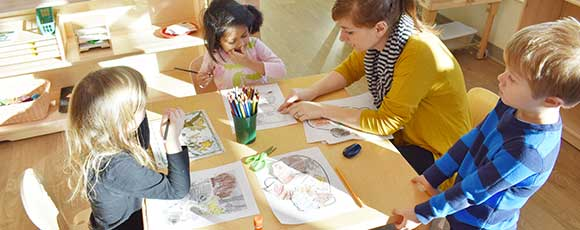 Photo of kids drawing with a teacher at the Bright Child Learning Center in Madison WI